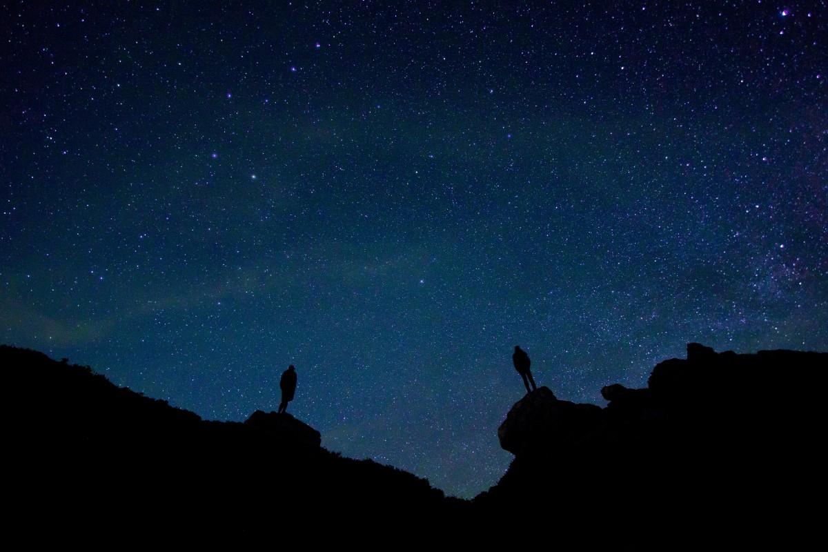 Due persone osservano un infinito cielo stellato