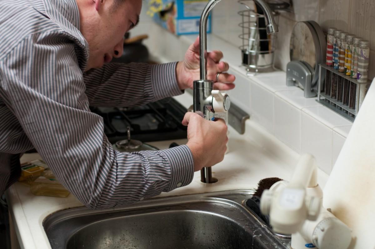 homme travail la personne mâle réparation cuisine cuisine évier professionnel métier ouvrier ouvrier artisan un service réparer mécanicien entretien Occupation fixation plomberie entrepreneur plombier bricoleur dépanneur Installation