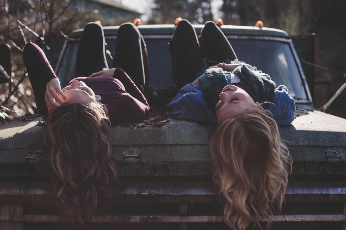 persona femmina brunetta giovane stile di vita bionda capelli ricci auto d'epoca ragazze amici contento dire bugie attraente immagine dello schermo stile di capelli