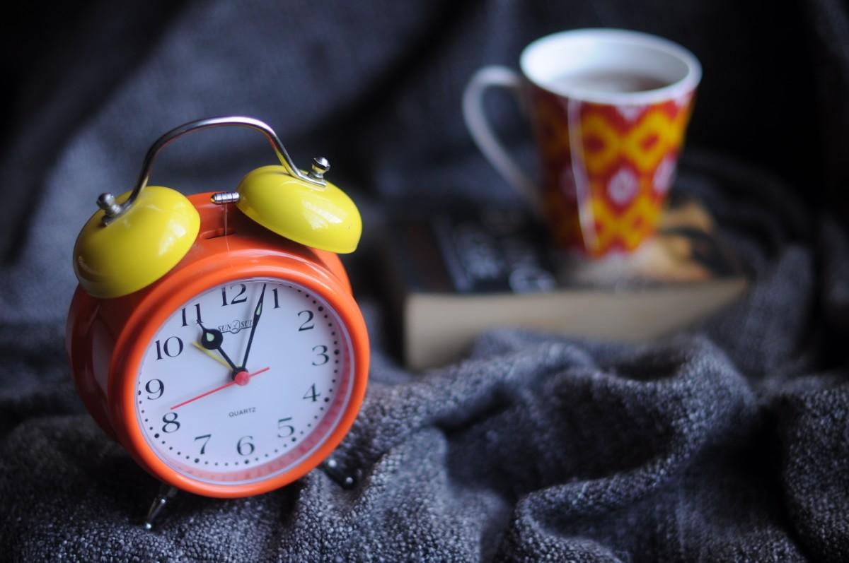 hand book clock time alarm clock red color yellow analog clock